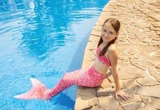 有桃红色尾巴的美人鱼女孩在游泳池边的岩石 库存照片