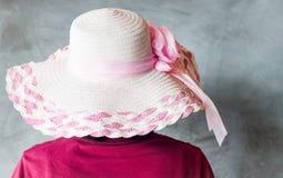 有桃红色帽子的妇女在灰色背景 库存图片