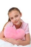 有桃红色心脏枕头的愉快的女孩 库存照片