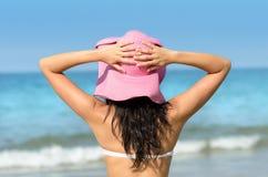 有桃红色星期日帽子的妇女在往海运的夏天 免版税库存照片