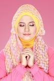 有桃红色服装佩带的hijab的年轻美丽的回教妇女 免版税库存照片