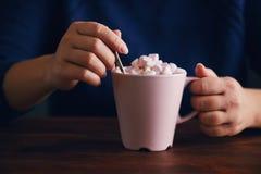 有桃红色杯子的妇女热巧克力和蛋白软糖 库存图片