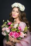 有桃红色构成和花的美丽的女孩 免版税图库摄影