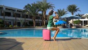 有桃红色案件的年轻女人在游泳场附近在旅馆里 旅行假期概念 股票视频