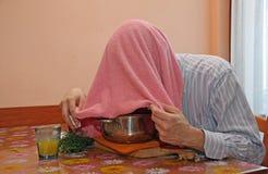 有桃红色毛巾的人呼吸凤仙花蒸气对待寒冷和流感 免版税库存照片