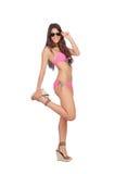有桃红色游泳衣和太阳镜的可爱的妇女 库存照片