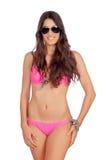 有桃红色游泳衣和太阳镜的可爱的妇女 库存图片