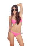 有桃红色游泳衣和太阳镜的可爱的妇女 免版税库存图片