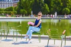 有桃红色牡丹的年轻巴黎人妇女在Tuileries 免版税库存图片