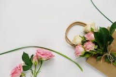 有桃红色玫瑰、绿色叶子和礼物袋子的女性书桌在白色背景 平的位置,顶视图 背景花光playnig 妇女` s天, 免版税库存图片