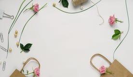 有桃红色玫瑰、绿色叶子和礼物袋子的女性书桌在白色背景 平的位置,顶视图 背景花光playnig 妇女` s天, 库存照片