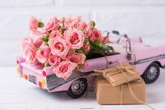有桃红色玫瑰和被包裹的箱子的减速火箭的汽车玩具有礼物的f 库存图片