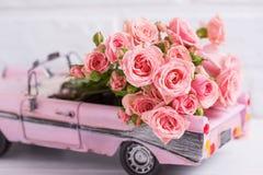 有桃红色玫瑰的减速火箭的汽车玩具开花反对桃红色Ñ † ршеу 免版税库存图片