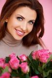 有桃红色玫瑰的华美的浅黑肤色的男人 免版税图库摄影