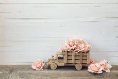 有桃红色玫瑰的木玩具卡车在白色的后面开花 免版税库存照片