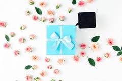 有桃红色玫瑰的闭合的蓝色礼物盒在白色背景 免版税库存照片