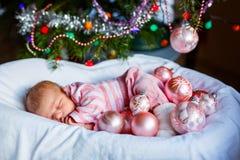 有桃红色球的一个星期的新出生的女婴临近圣诞树 免版税库存照片