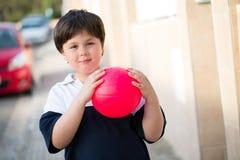 有桃红色球的小男孩在stree 库存图片
