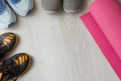 有桃红色瑜伽的橙色,蓝色和灰色体育鞋子 库存图片