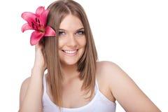 有桃红色百合的微笑的妇女 免版税库存图片