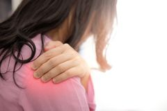 有桃红色的布料的亚裔妇女肩膀痛苦 免版税库存照片