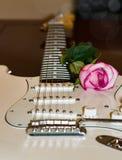 有桃红色的白色吉他上升了在soundboard一边 库存照片