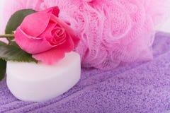 有桃红色的肥皂上升了在一块紫色毛巾顶部,与桃红色阵雨吹 免版税库存照片
