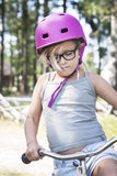 有桃红色盔甲、黑玻璃和自行车的女孩 库存图片
