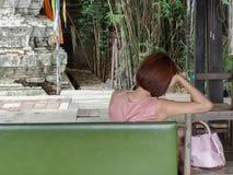 有桃红色礼服和桃红色提包想法的单独开会的孤独的绝望妇女在一条绿色长凳 免版税库存图片