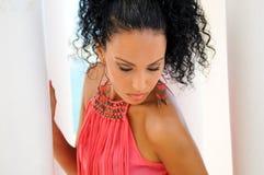 有桃红色礼服和耳环的黑人妇女。蓬松卷发发型 免版税库存照片