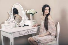 有桃红色礼服和长的黑发的美丽的愉快的妇女在她的在她的摆在党面前的梳妆台附近的屋子里 免版税图库摄影