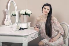 有桃红色礼服和长的黑发的美丽的愉快的妇女在她的在她的摆在党面前的梳妆台附近的屋子里 库存图片