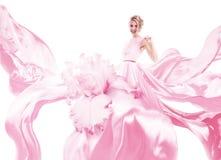 有桃红色礼服的愉快的妇女在光 免版税库存图片