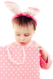 有桃红色耳朵兔宝宝和袋子的小女孩。 免版税库存图片