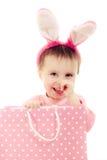 有桃红色耳朵兔宝宝和袋子的小女孩。 库存照片