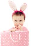 有桃红色耳朵兔宝宝和袋子的小女孩。 图库摄影