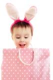 有桃红色耳朵兔宝宝和袋子的小女孩。 免版税库存照片