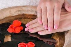 有桃红色胶凝体的女孩手擦亮在手指钉子的修指甲水面上在碗 库存照片
