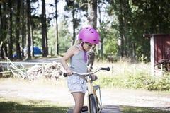 有桃红色自行车盔甲的学会的孩子骑自行车 图库摄影