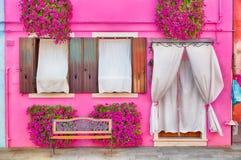 有桃红色花和植物的桃红色房子 在窗口下的好的长凳 五颜六色的房子在威尼斯,意大利附近的Burano海岛 免版税库存图片