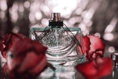 有桃红色花玫瑰的香水瓶 库存图片