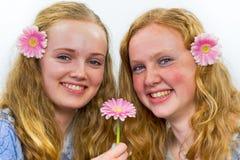 有桃红色花的两个姐妹在头发 免版税库存照片