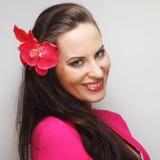 有桃红色花的愉快的妇女在头发 库存图片