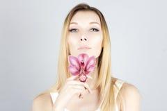 有桃红色花的秀丽妇女在手中 清楚和新鲜的皮肤 秀丽表面 免版税图库摄影