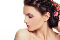 有桃红色花的美丽的妇女在发型 免版税库存照片