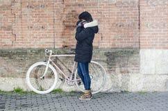 有桃红色葡萄酒自行车的妇女有白色轮子的 库存图片