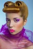 有桃红色薄纱和糖果的色的时尚秀丽妇女上色了在她的嘴唇的珍珠和在蓝色背景的幻想金黄发型 库存图片