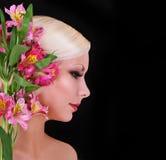 有桃红色虹膜的美丽的白肤金发的少妇开花在黑色,时装模特儿 库存图片