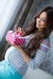有桃红色赃物的愉快的未来母亲在手中 库存图片