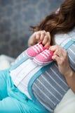 有桃红色赃物的愉快的未来母亲在手中 库存照片